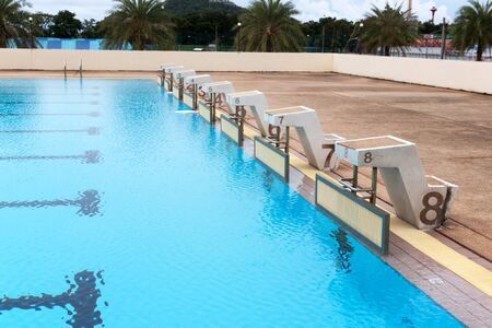 blue water wave in swimming pool reflects with sunlight , blue tile ceramic to swimming race and water sports.