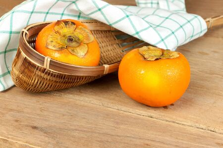 tacky: Persimmon yellow color ripe fruits on wood table