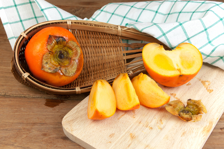 tacky: Persimmon yellow color ripe split fruits on wood table