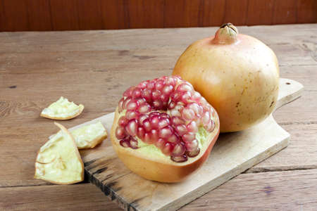 dissect: Pomegranate fruit cut dissect on wooden background.