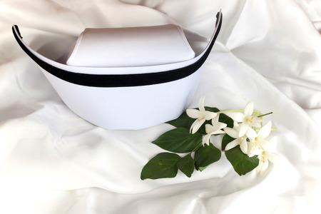 registered nurse: Hat nurse white and Millingtonia hortensis flowers on white fabric. symbol of nursing thailand and Thai traditional medicine. Stock Photo