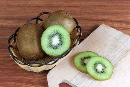 fresh kiwi  fruits and slices of kiwi fruit in basket on wood