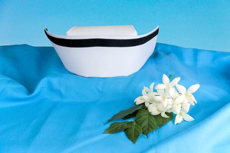 registered nurse: Hat nurse white and Millingtonia hortensis flowers on blue fabric. symbol of nursing thailand and Thai traditional medicine.
