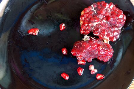 dissect: Carmine Pomegranate fruit cut dissect on black dish