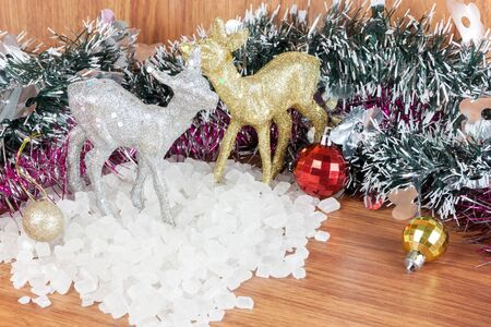 crystalline gold: Deer color silver and gold on a pile of white crystalline. Red and yellow Christmas Balls Ornaments on wood,