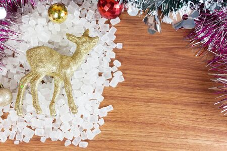 crystalline gold: Deer color gold on a pile of white crystalline. Red and yellow Christmas Balls Ornaments on wood,