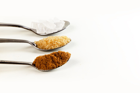 Brown cane sugar in a metal spoon on the white background. Pure cane sugar for natural. no additives. Stock Photo