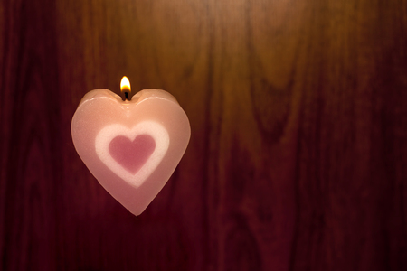 heart burn: Candles shape heart pink color were lit on wood background. Love symbol for Valentines day concept.