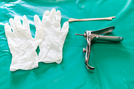 Colposcop, spatula and Medical gloves on a clean green blanket (Equipment vaginal speculum) for (Pap smear) gynecology inspect EXAMINATION Cervical cancer Stock Photo