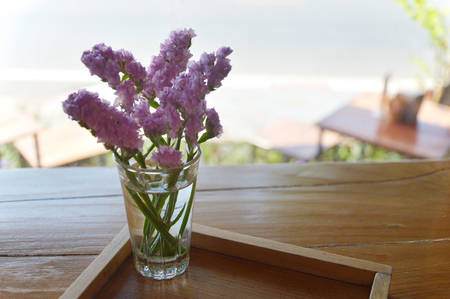 Statice flowers in a little glass on a wood tray. Backlit photos. Stock Photo