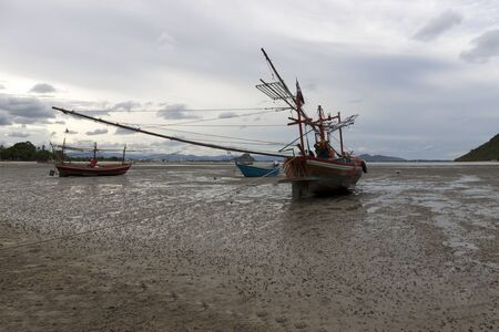 Fishing wood boat parked on Beach, the seaside in Thailand