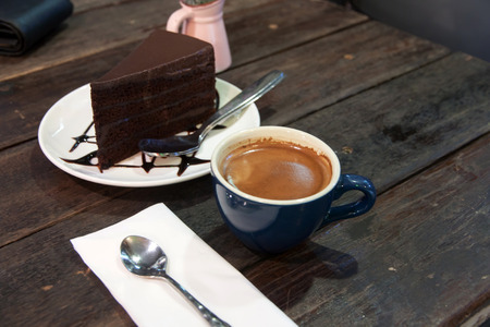 Coffee Break, chocolate cake and  espresso on wood table