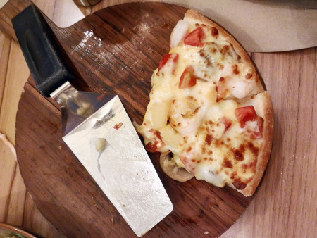 Two pizzas on wooden tray and a lap pizza on wooden table Stock Photo