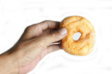 Food and Bakery. Man Hand Holding Delicious Fresh and Sweet Donut glazed with a sugar icing on white background. Stock Photo