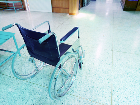 Empty wheelchair resting in the lobby of a hospital. healthcare and disability image Stock Photo