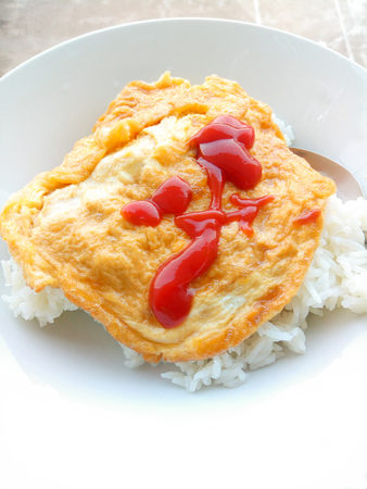 Omelet rice topped with ketchup in white plate. Thai Street Food Stock Photo