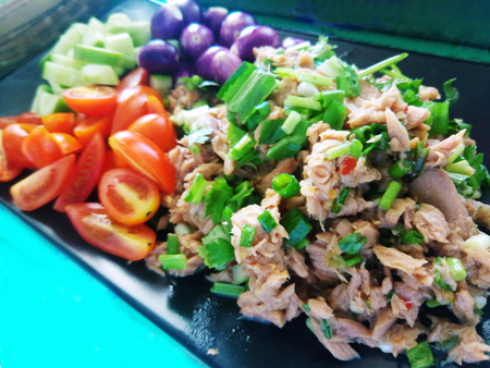 Tuna salad spicy eat with tomatoes, eggplant and cucumber in black dish. Thai spicy food. Stock Photo