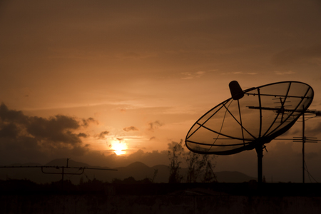 Small satellite dish to receive signals from satellite dish large Satellite in evening sky background Stock Photo