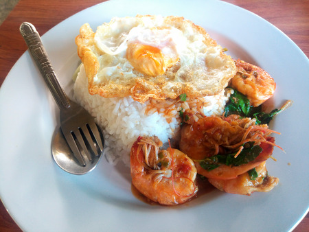 Street food in Thailand. rice with stir-fried of shrimp and basil leaf with fried egg hot and spicy. Stock Photo