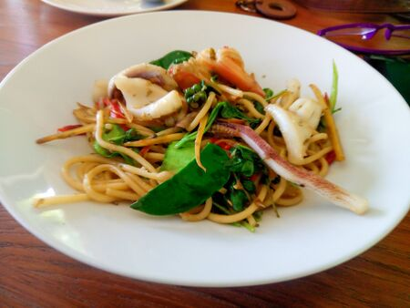 spicy stir fried spaghetti seafood with pepper and basil leaf on the white plate