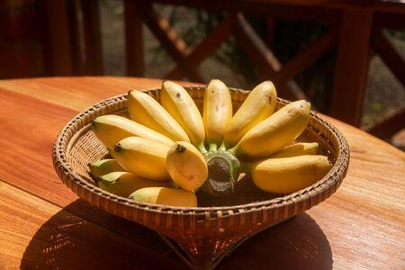 golden bananas or Lady Finger banana in weave basket on wood table. healthy fruit food.