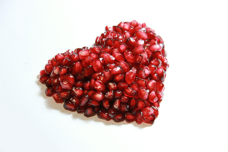 The plenty of Pomegranate fruit arrange to heart shape on the white  photo