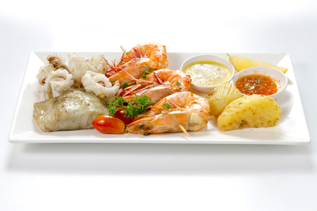 Variation of Roasted Seafood Contain Grilled Jumbo Prawns, Calamari Squids and Barracuda Fish Garlic Pepper with Spicy Chili Sauce, Lemon, Tomatoes, Potatoes, Side View, Selective Focus at Food. Stock Photo