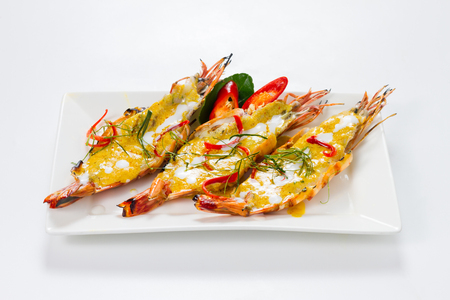 Three Pieces of Big Shrimps with Panang Curry Thai Style on White Porcelain Square Plate, Isolated on White Background with Shadow. High Angle Front Side View, Selective Focus at Food.