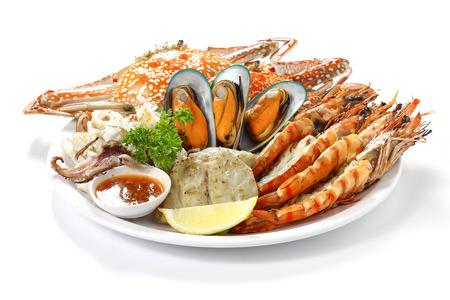 Gebratene gemischte Meeresfrüchte enthalten blaue Krabben, Miesmuscheln, große Garnelen, Kalmar-Kalmare und gegrillter Barracuda-Fisch-Knoblauch mit würziger Chili-Sauce und Zitrone auf dem Teller, lokalisiert auf weißem Hintergrund mit Schatten.