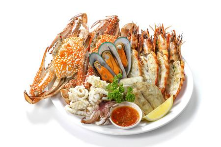 Gegrilde gemengde zeevruchten bevatten blauwe krabben, mosselen, grote garnalen, calamari inktvissen en geroosterde barracuda vis knoflook met pittige chili saus en citroen op schotel, geïsoleerd op een witte achtergrond met schaduw. Stockfoto