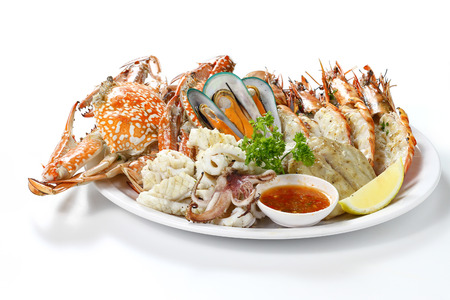 Grilled Mixed Seafood Contain Big Prawns, Mussels, Blue Crabs, Calamari Squids and Roasted Barracuda Fish Garlic with Spicy Chili Sauce and Lemon on Plate, Isolated on White Background with Shadow.