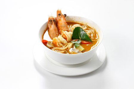 Spicy Sour Shrimps Soup with Round Noodles Thai Style (Tom Yum Kung) in White Bowl, Isolated on White Background with Shadow, Tilted High Angle Front Side View. Selective Focus at Front of Food.