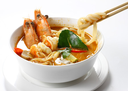 Spicy Sour Big Shrimps Soup with Udon Noodles Thai Style (Tom Yum Kung) in White Bowl, Wooden Chopsticks are Pinching the Noodles, Isolated on White Background with Shadow Tilted High Angle Front View