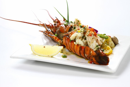 expensive: Stir-fried Lobster with Garlic & Butter Sauce on white square porcelain plate Isolated on white background with shadow Tail Side view, Luxury Seafood. Selective Focus. Stock Photo