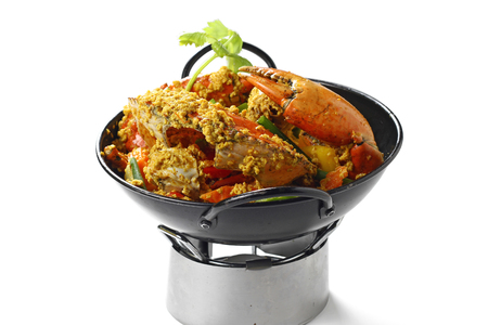 Stir-fried Big Mud-Crab (Mangrove-Crab or Black-Crab) in Yellow Curry Powder on Black Pan on the Small Oven, Isolated on White Background, High Angle Top Side View, Selective Focus at Food.