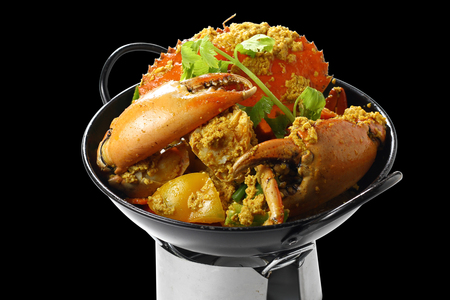 Stir-fried Giant Mud-Crab (Mangrove-Crab or Black-Crab) with Yellow Curry Paste on Black Pan on the Mini Oven, Isolated on Black Background, High Angle Side View, Closeup Selective Focus at Food. Stock Photo