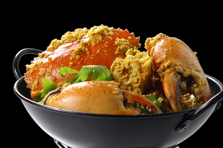 Stir-fried Giant Mud-Crab (Mangrove-Crab or Black-Crab) in Yellow Curry Powder on Black Pan on the Mini Oven, Isolated on Black Background with Clipping Path, High Angle Side View, Close up at Food. Stock Photo