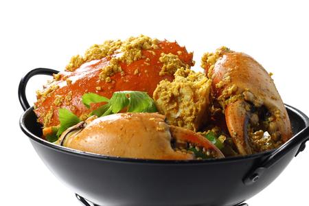 Roergebakken Giant Mud-Crab (mangrove-krab of zwarte krab) met gele kerriepoeder op zwarte pan op de mini-oven, geïsoleerd op een witte achtergrond, hoog hoek bovenaanzicht, selectieve focus op voedsel.