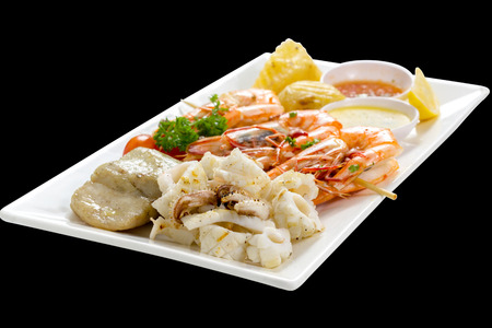 Mixed Roasted Seafood (Platter Set) Contain Grilled Big Shrimps, Calamari Squids and Barracuda Fish Pepper Garlic with Spicy Chili Sauce & Potatoes, Front Side View, Isolated on Black Background.