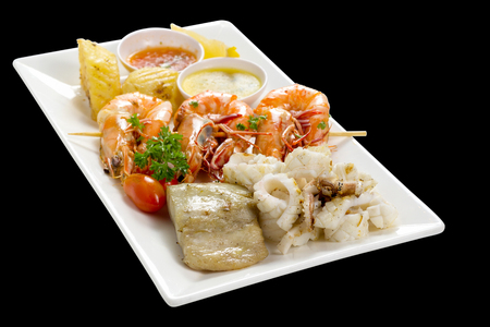Mixed Roasted Seafood (Platter Set) Contain Grilled Big Shrimps, Calamari Squids and Barracuda Fish Garlic Pepper with Spicy Chili Sauce and Potatoes, High Angle View, Isolated on Black Background.