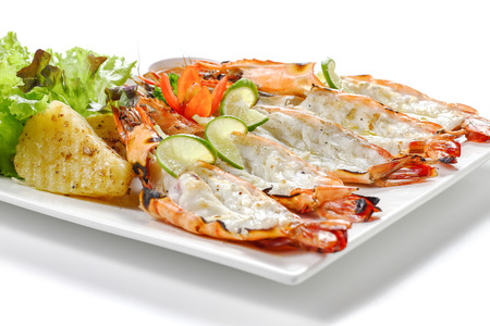 Grilled sliced black tiger shrimps with baked potatoes, slice of limes, fresh vegetables and chili sauce on square plate, isolated on white background Close-up macro side view Focus at middle of food. Archivio Fotografico