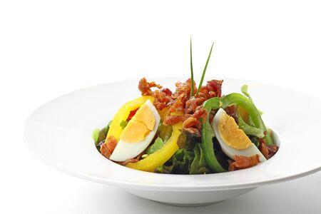Fresh Caesar Salad with Deep-fried Bacon and Boiled Egg on White Circle Plate, Isolated on White Background with Shadow. Close-up Low Angle Side View, Selective Focus at Front. Imagens