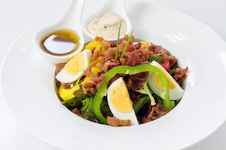 Fresh Caesar Salad with Deep-fried Bacon and Boiled Eggs & Salad-dressing on White Porcelain Round Plate, on White Background with Shadow. Close-Up High Angle Side View, Selective Focus at Food. Imagens