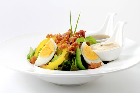 Fresh Caesar Salad with Deep-fried Bacon and Boiled Egg on White Porcelain Circle Plate, on White Background with Shadow. Close-Up Low Angle Side View, Selective Focus at Food. Imagens