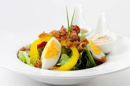 Fresh Caesar Salad with Deep-fried Bacon and Boiled Eggs on White Porcelain Round plate, on White Background with Shadow. Close Up Low Angle Side View, Selective Focus at Food.