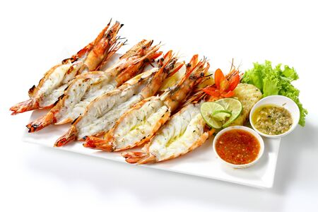 Grilled 5 black tiger shrimps with boiled potatoes, slice of lime, tomato fresh vegetables and 2 chili seafood sauce on white square plate isolated on white background with shadow high angle top view 版權商用圖片