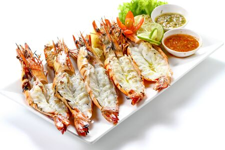 Grilled 5 black tiger shrimps with boiled potatoes, slice of lime, tomato fresh vegetables and 2 chili seafood sauce on white square plate isolated on white background with shadow high angle side view
