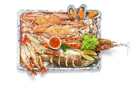Roasted Mixed Seafood Platter Set contain Lobster, Fish, Blue Clab, Big Prawns, Mussels Clams and Calamari Squids with pieces of lemon & vegetables, Isolated on white background with Shadow, Top view.