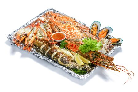 Grilled Mixed Seafood platter Set : Lobster, Fish, Blue Clab, Big Prawn, Mussel Clam, Calamari Squids with pieces of lemon & vegetable isolated on white background with shadow High angle top side view