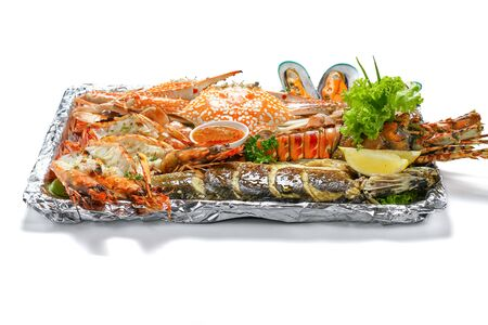 Grilled Mixed Sea-food Big Set contain Lobster Sea Perch Fish Blue Clab Big Shrimps Mussels Clams Calamari Squids with pieces of lemon & vegetables on white background with shadow low angle side view.